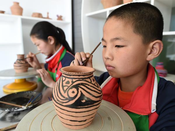 临洮县金泽小学的小学生在绘制陶品