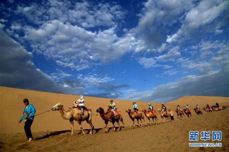 游客在甘肃省敦煌市鸣沙山月牙泉景区参观游览